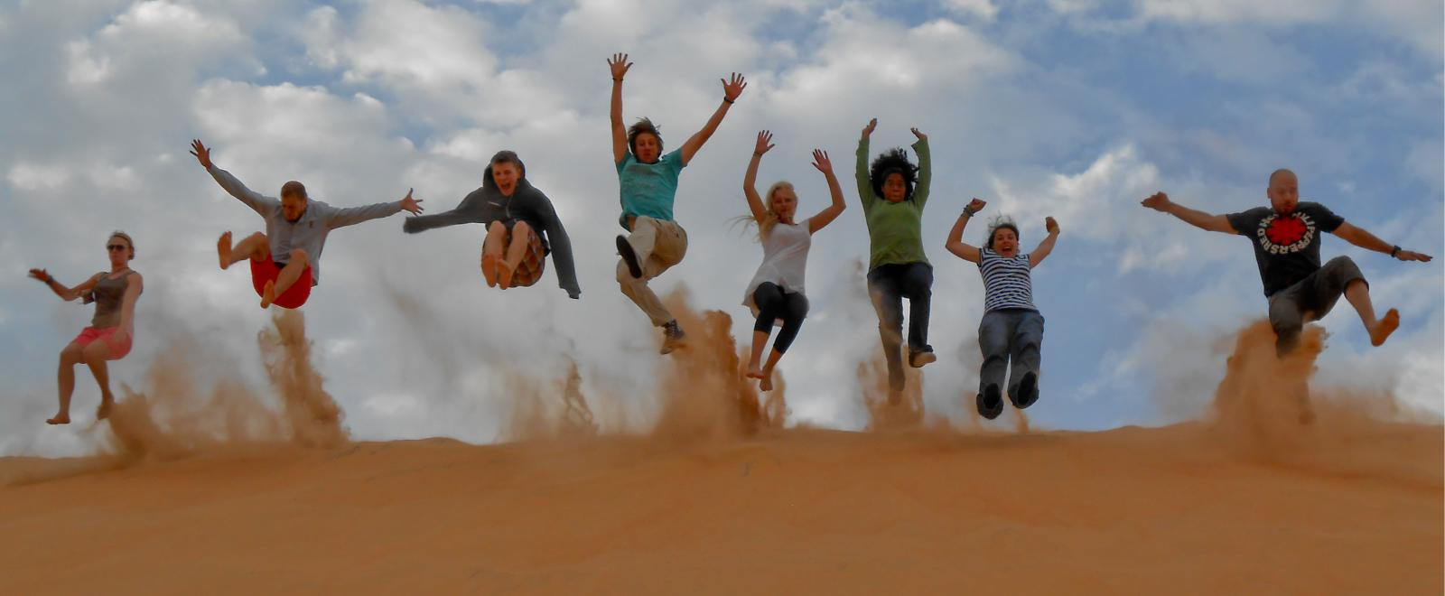 A group of volunteers jumping on a sand dune in Senegal